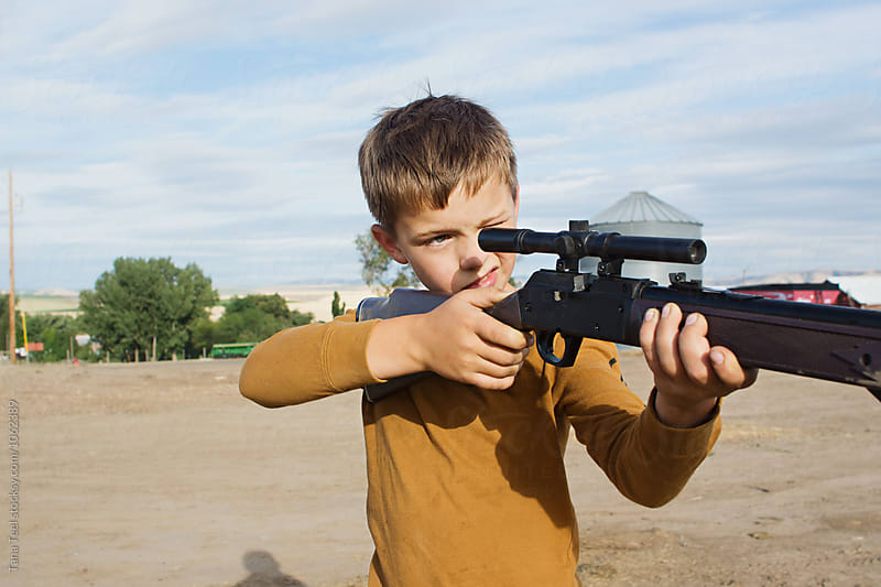 boy aims bb gun at target by Tana Teel for Stocksy United