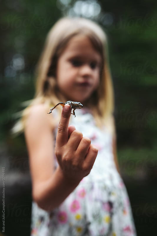 Young girl with frog on her finger by Rob and Julia Campbell for Stocksy United