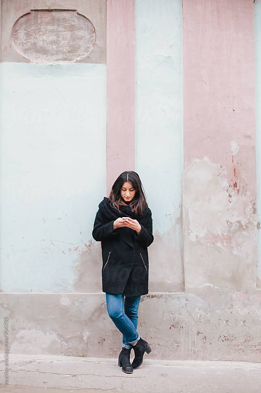 Woman using her mobile phone outdoors by Marija Mandic for Stocksy United