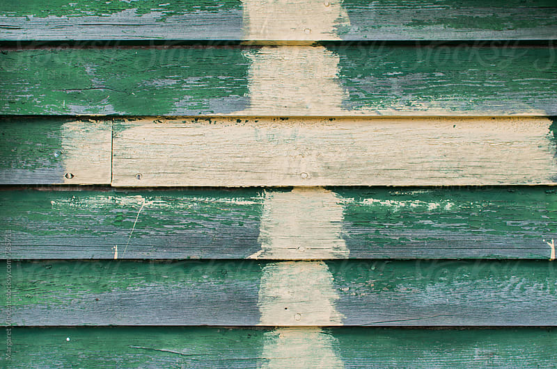 green siding with painted cross by Margaret Vincent for Stocksy United