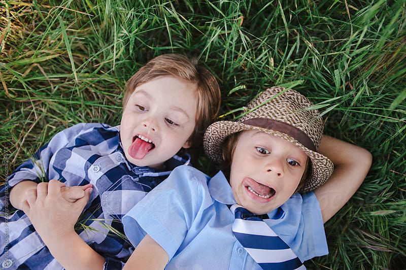Stylish young brothers being playful in the grass by Kristin Rogers Photography for Stocksy United