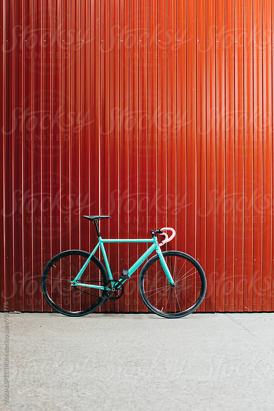 Minimalist Turquoise Fixed Gear Bicycle Leaning Against Shiny Red Wall by VISUALSPECTRUM for Stocksy United