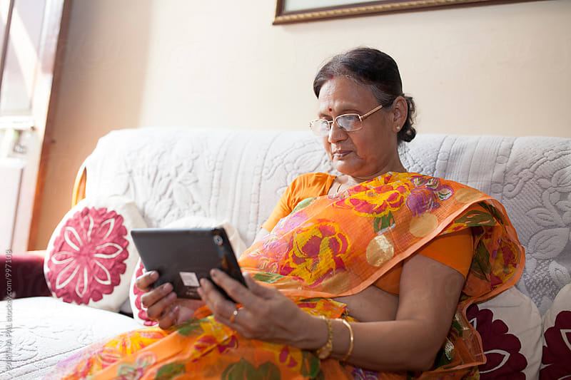 Indian aged woman using Tablet by PARTHA PAL for Stocksy United
