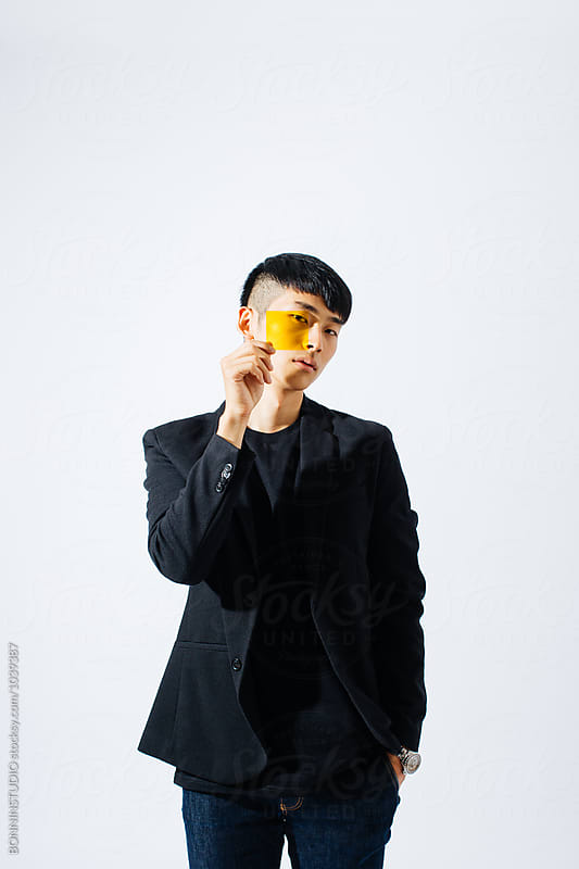 Portrait of an asian man holding a yellow glass in front his face. by BONNINSTUDIO for Stocksy United