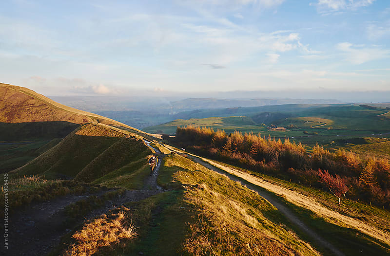 Male running on a mountain ridge at sunset. Derbyshire, UK. by Liam Grant for Stocksy United