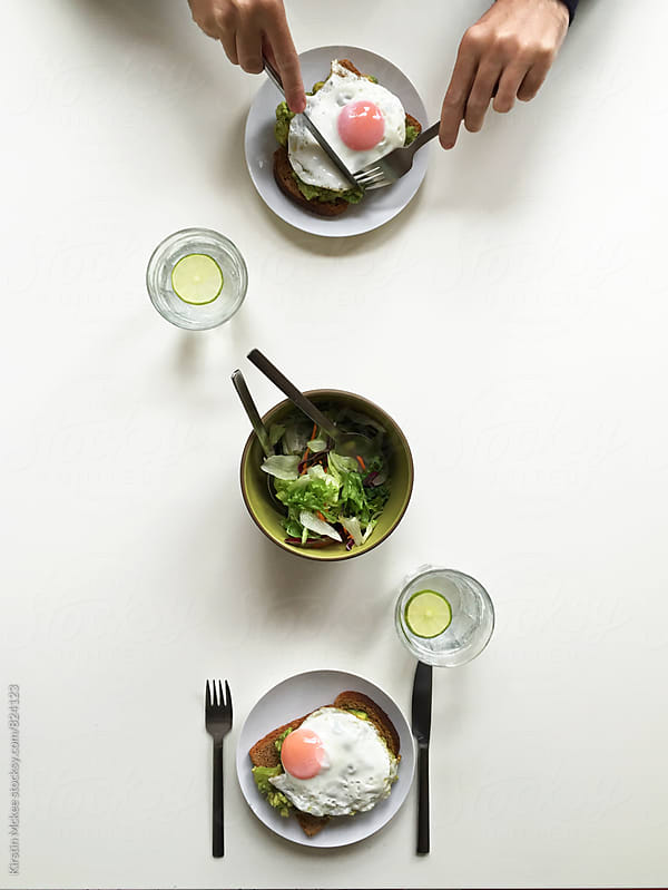 Couple sharing fried egg, avocado toast and a salad for lunch by Kirstin Mckee for Stocksy United