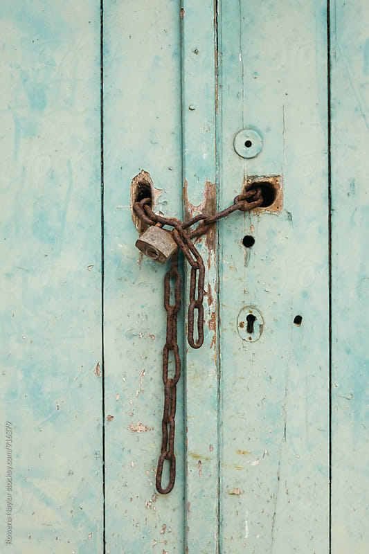 Old rusty chain and lock on shed door by Rowena Naylor for Stocksy United