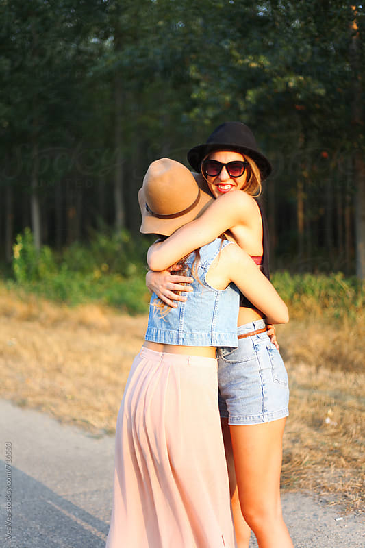 Two beautiful female friends hugging outdoors by Marija Mandic for Stocksy United