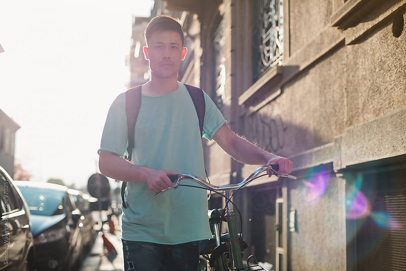Asian man walking in the city city with a bike by GIC for Stocksy United