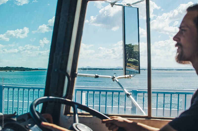Man driving a bus over coastal bridge by Dominique Chapman for Stocksy United