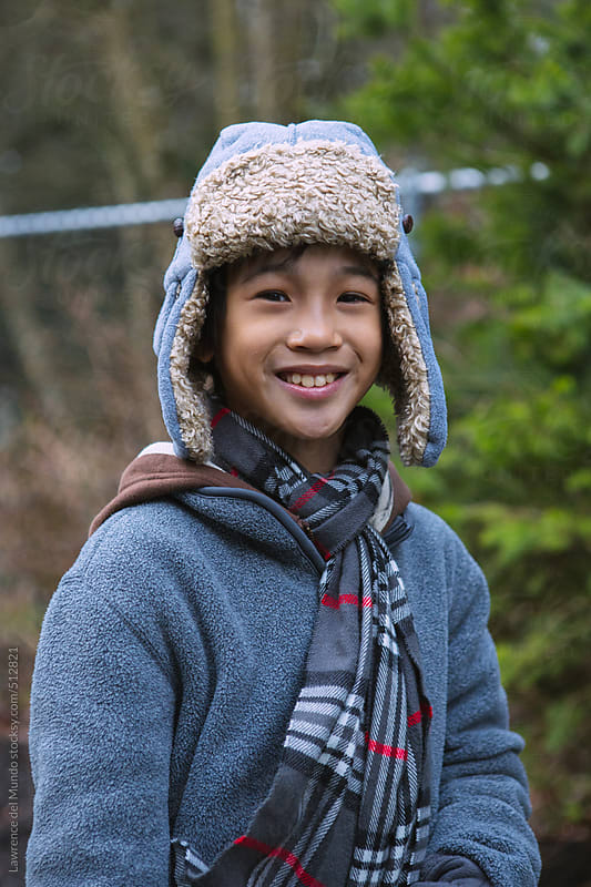 Asian kid in winter clothes smiling at the camera by Lawrence del Mundo for Stocksy United