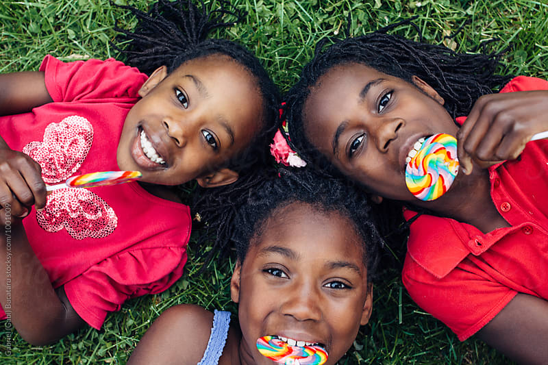Three African American girls with rainbow lollipops on the grass by Gabriel (Gabi) Bucataru for Stocksy United