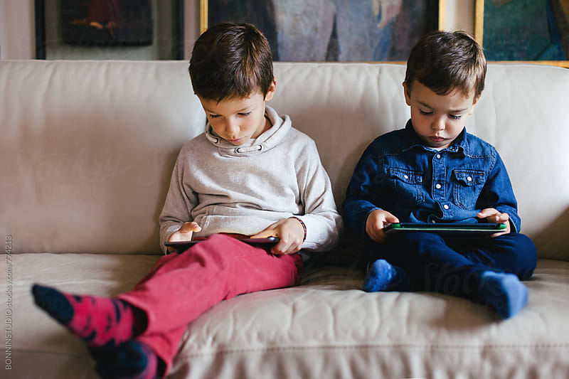 Little brothers using their digital tablet sitting on the sofa. by BONNINSTUDIO for Stocksy United