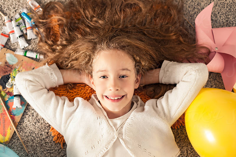 Smiling Girl Lying on the Floor by Lumina for Stocksy United