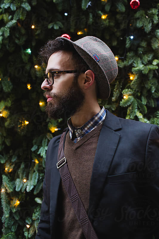 Portrait of young man with beard with colored lights behind by michela ravasio for Stocksy United
