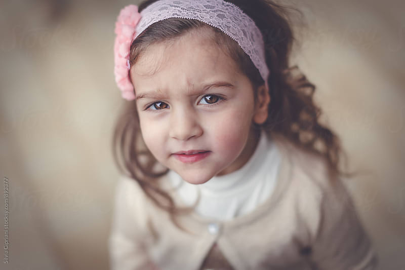 Portrait of a cute little girl looking at the camera by Silvia Cipriani for Stocksy United