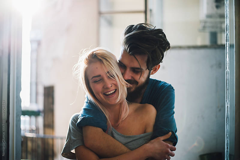 Pretty Blond Woman Smiling While Her Boyfriend is Hugging Her. by Nemanja Glumac for Stocksy United