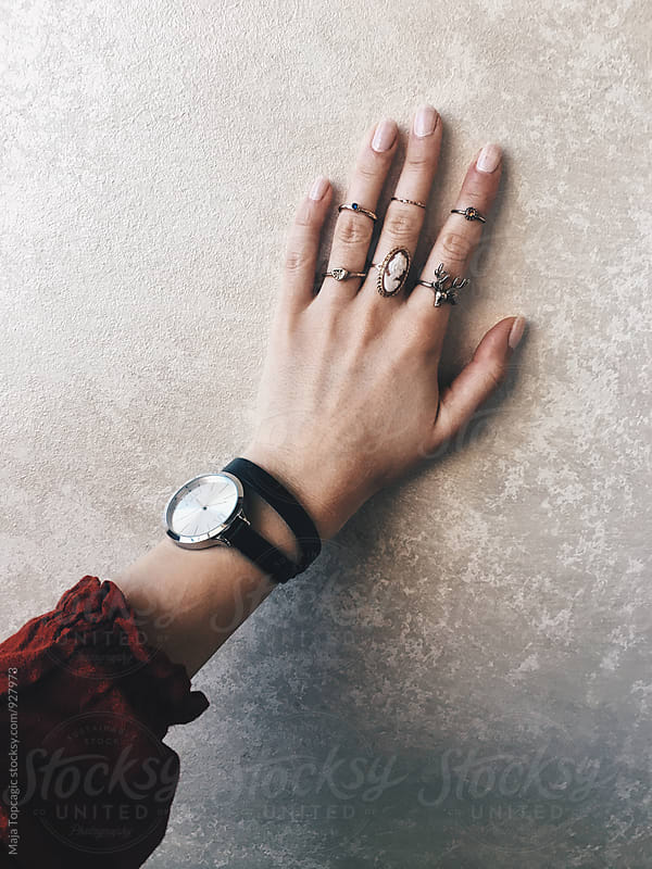 Female hand with a lot of rings against a textured background by Maja Topcagic for Stocksy United