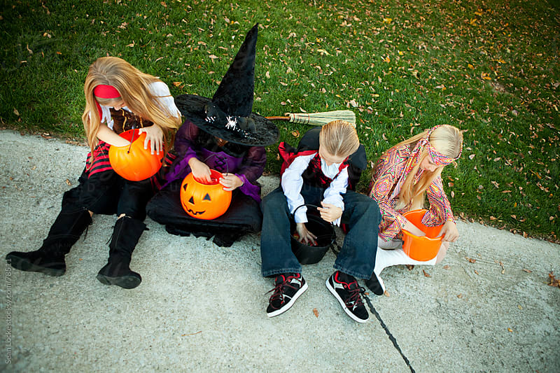 Halloween: Kids Take a Break from Trick or Treating by Sean Locke for Stocksy United