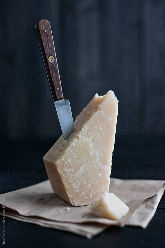 Food: Grana Padano, italian cheese with knife by Ina Peters for Stocksy United