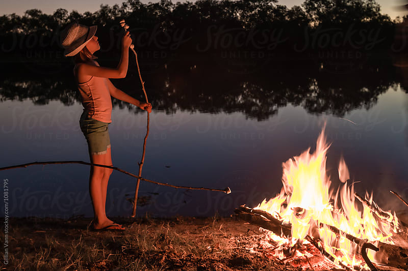 tween girl loading up a stick for toasting marshmallows over a campfire at night by Gillian Vann for Stocksy United