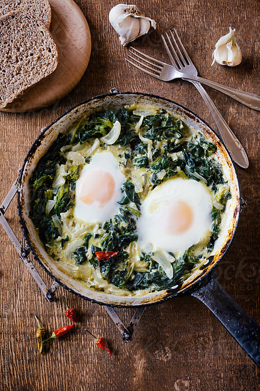 Skillet-baked eggs with spinach by Pixel Stories for Stocksy United
