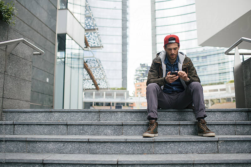 Young man using a smartphone outdoor by Davide Illini for Stocksy United