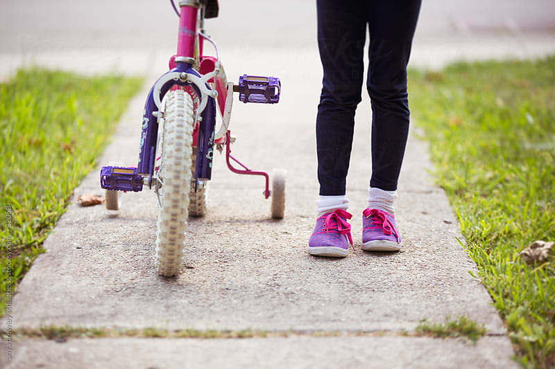 The feet of a young girl and the wheel of her bike by anya brewley schultheiss for Stocksy United