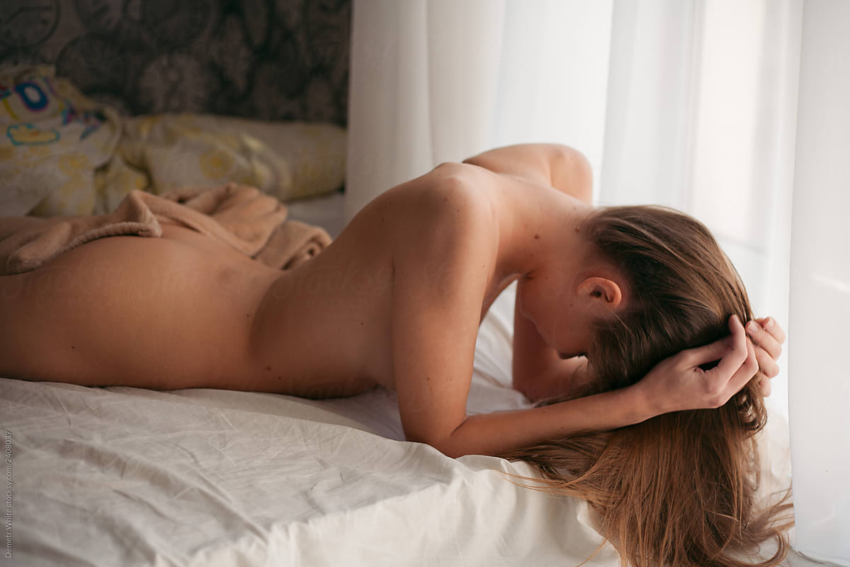 naked women on the bed collects hair on the bed by Dmytro ...
