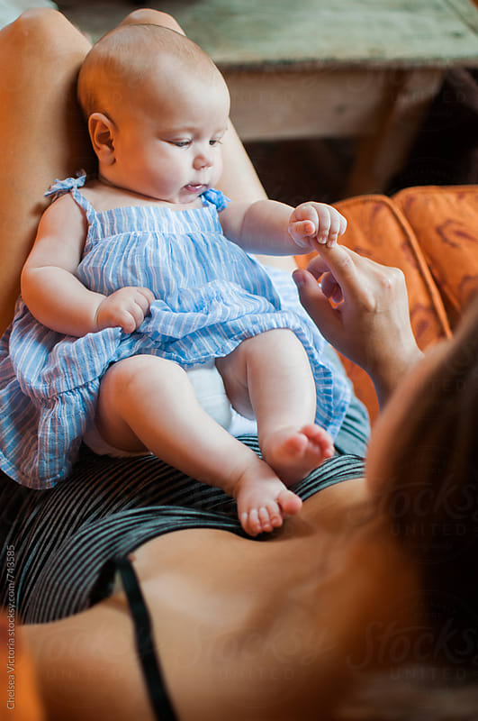 A baby touches her mothers hand by Chelsea Victoria for Stocksy United