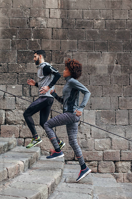 Young multiethnic couple running of old steps outside. by BONNINSTUDIO for Stocksy United