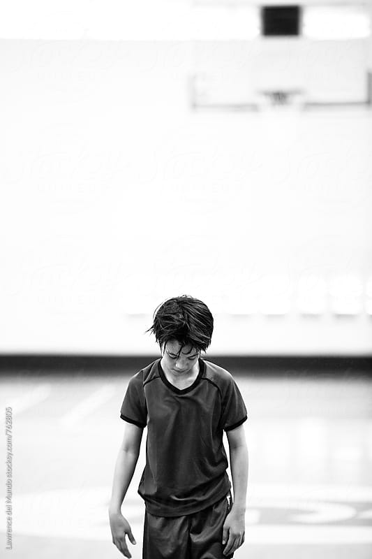 Black and white portrait of young boy about to shoot the basketball inside an indoor gymnasium by Lawrence del Mundo for Stocksy United