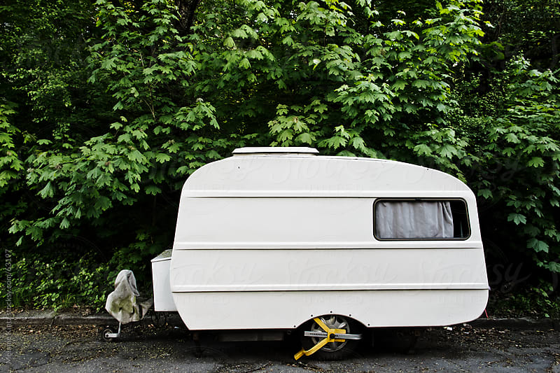 Parked oldfashioned Camper-trailer before green trees by Melanie Kintz for Stocksy United