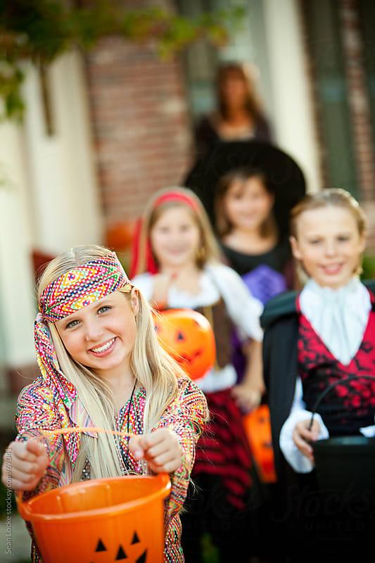 Halloween: Little Girl Holds Out Halloween Bucket by Sean Locke for Stocksy United