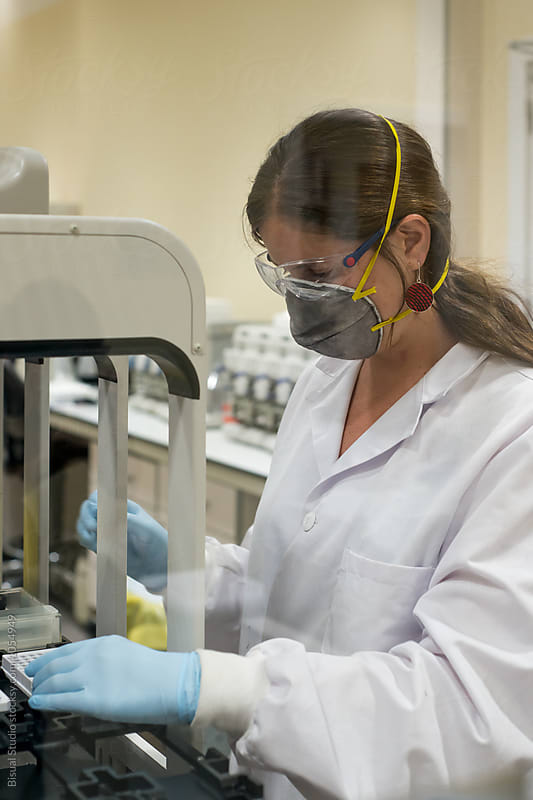Female scientist working with a genome sequencing machine in a DNA laboratory by Bisual Studio for Stocksy United