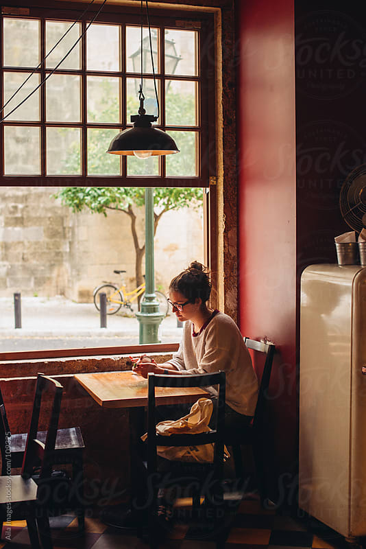 Girl sitting in a cafe by Aila Images for Stocksy United
