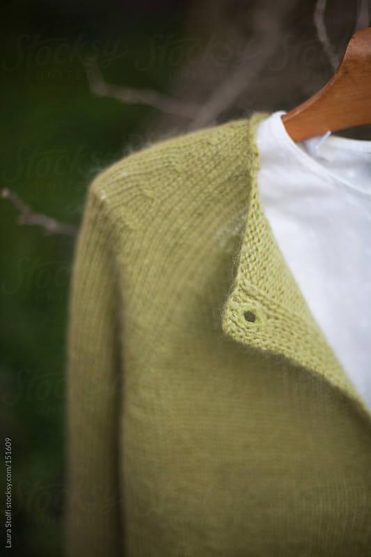 Green woolen cardigan hanging in garden  by Laura Stolfi for Stocksy United