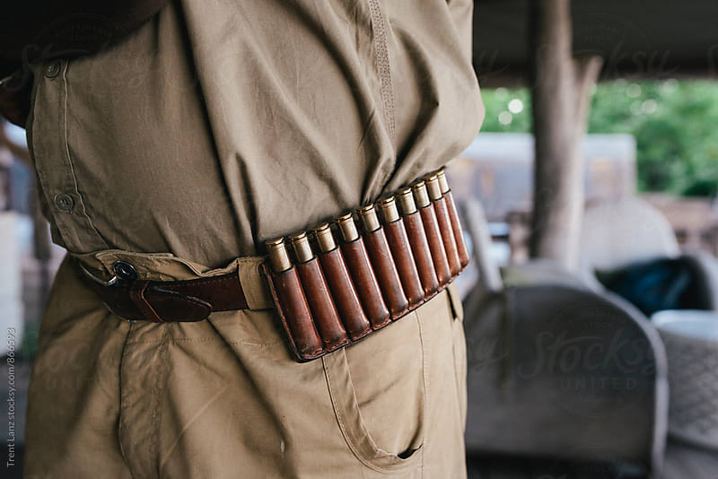 Close-up of safari man wearing belt with bullet cartridges by Trent Lanz for Stocksy United