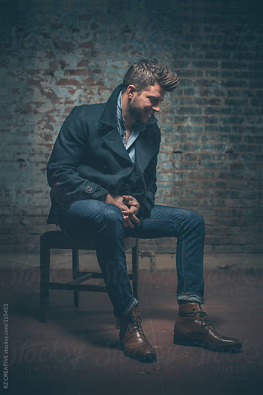 Portrait of a stylish man sitting on a chair against a brick wall background. by RZ CREATIVE for Stocksy United