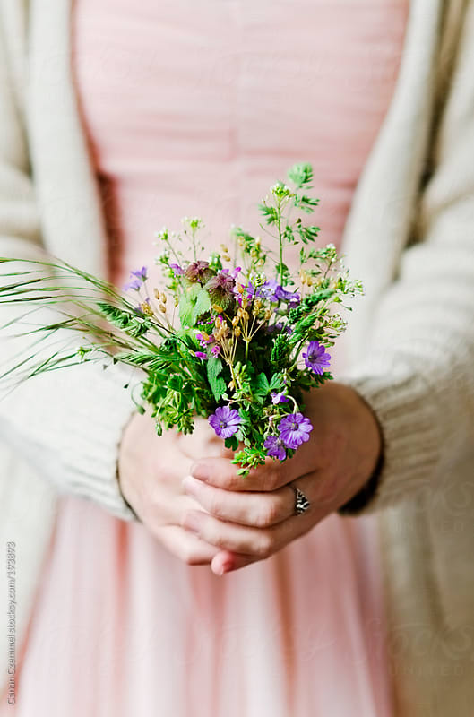 young woman holding a bunch of field flowers by Canan Czemmel for Stocksy United