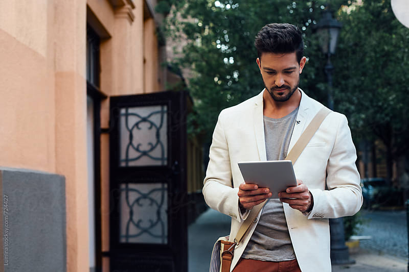 Handsome Man Using a Tablet on the Street by Lumina for Stocksy United