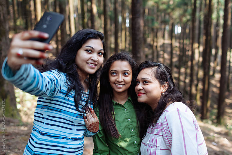 Group of friends taking selfie in the forest by Saptak Ganguly for Stocksy United