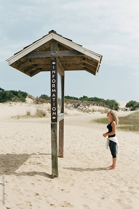 Woman looking at tourist information board on the beach by Jakob for Stocksy United