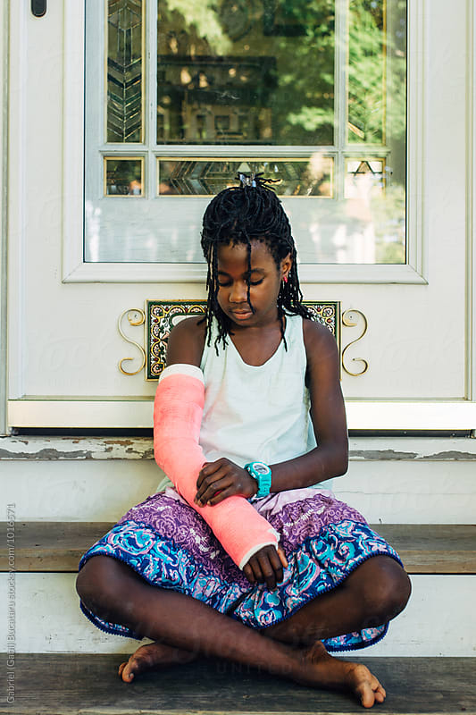Black girl looking at her pink cast by Gabriel (Gabi) Bucataru for Stocksy United