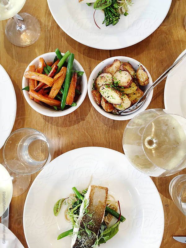 overhead view of restaurant lunch, with seafood, vegetables and white wine by Gillian Vann for Stocksy United