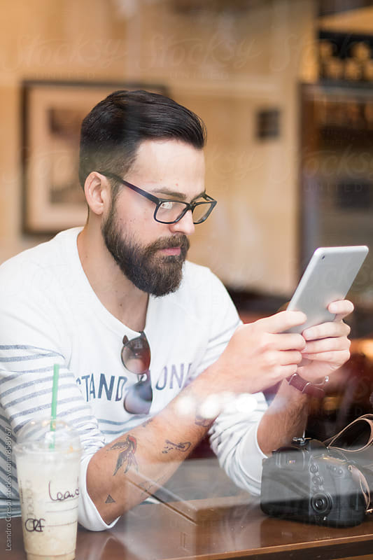 Young man using tablet in a bar by Leandro Crespi for Stocksy United