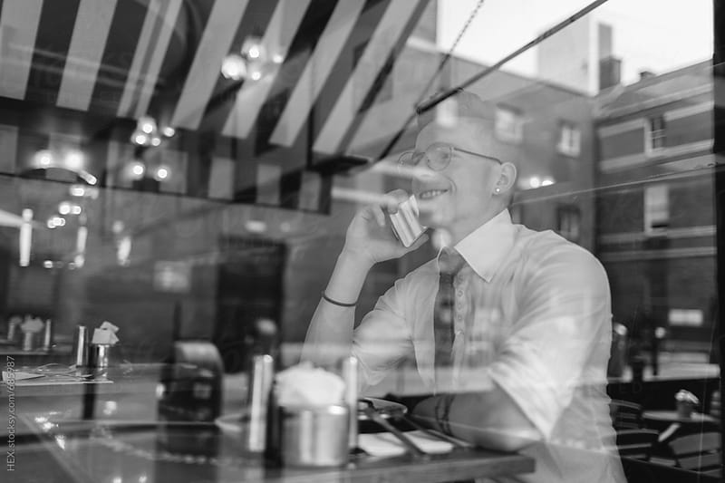 Businessman on the Phone Through a Coffee Shop Window  by HEX . for Stocksy United