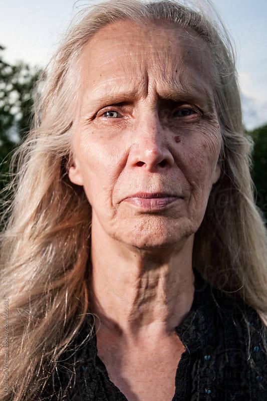 An elderly blonde woman with windblown hair by J Danielle Wehunt for Stocksy United