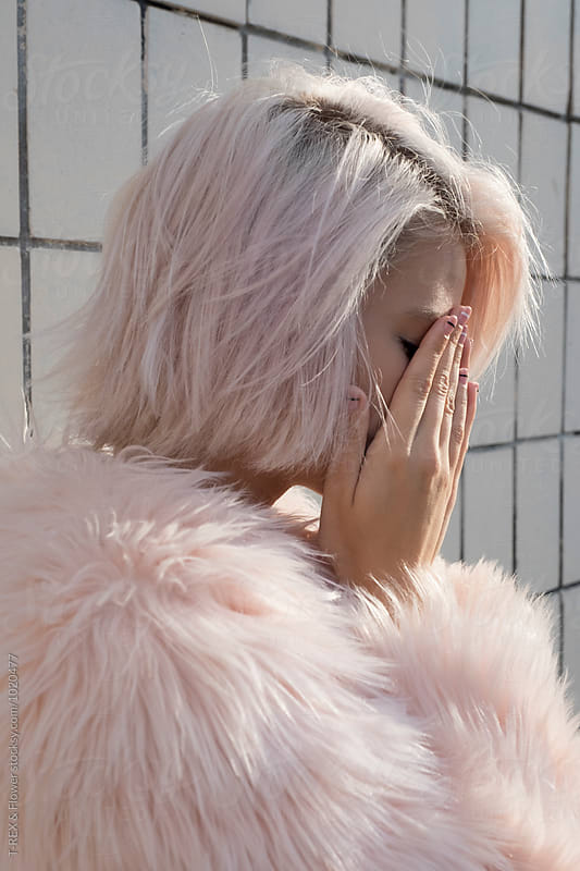 Close-up of sad blonde girl covering face with hands