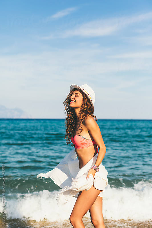 Attractive woman with white scarf and hat, enjoying the water and the sunlight on the beach by Aleksandar Novoselski for Stocksy United